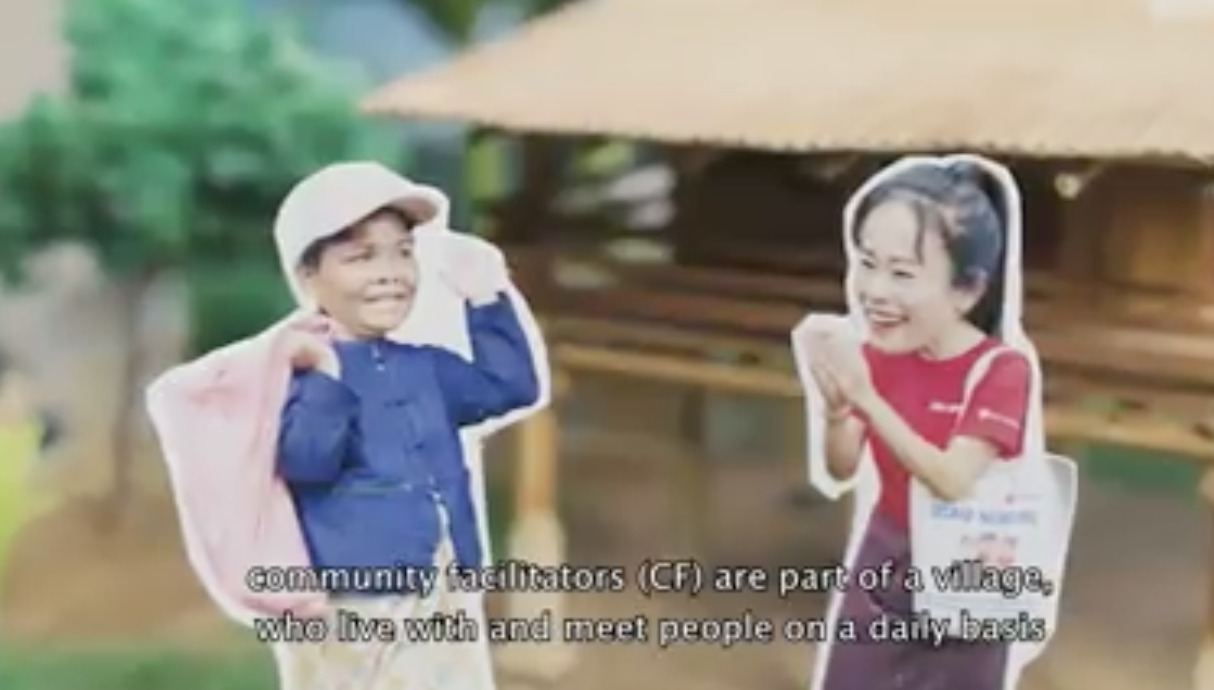 Video still of two Lao people in a village greeting each other.